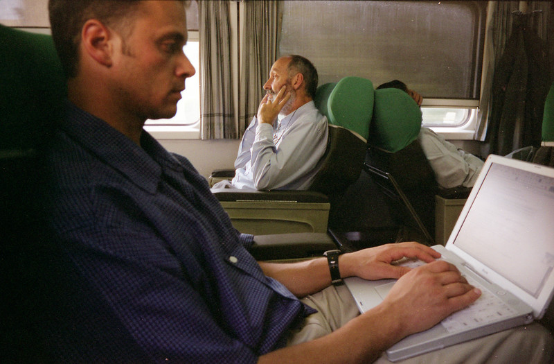 (Oct. 2003 Egypt) Jim Chesnutt of News Corps Internation works on a story as Bob Ludwig, President of Hands Along The Nile, conducts an interview with NPR on the train to Minia.<br /> Photo: Michael Rieger