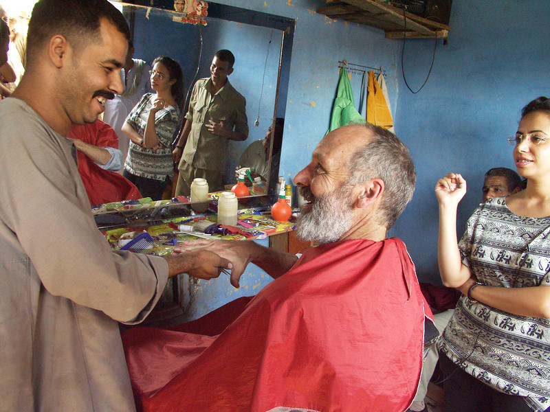 """(Oct 8,2003 Ashmoneen, Egypt) -- Robert Ludwig, president of Hands Along The Nile, recieves a hair cut in Ashomeen Village.  This business is one of many who has benifited from the micro loan program at CEOSS.<br /> Photo: Michael Rieger<br /> ( <a href=""""http://www.newscorps.com"""">http://www.newscorps.com</a>)<br /> 720-331-6402"""