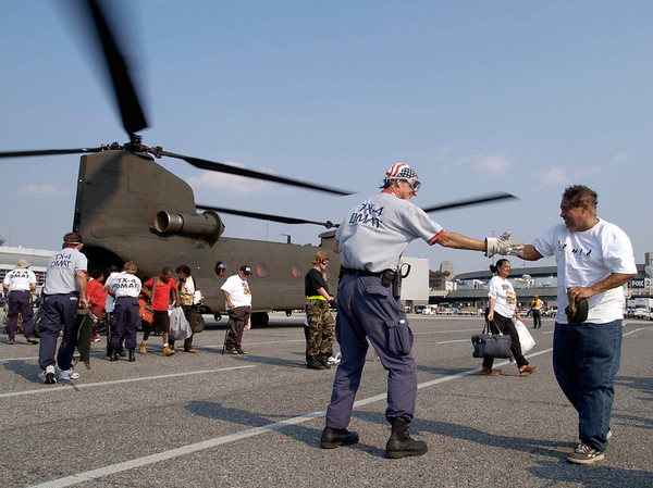 """(Sept. 3, 2005 New Orleans) -- Kent Conway of FEMA""""S  D-MAT   Texas-4 helps people as they arive at New Orleans Airport for trans port to other states shelters.  D-MAT TX-4 was one of first to set up the Medical falicity there.<br /> Photo: Michael Rieger/FEMA"""