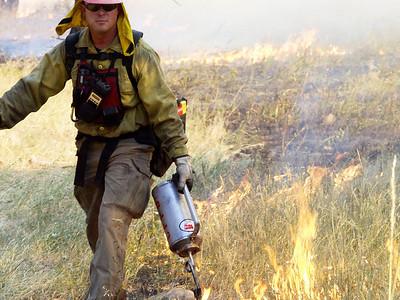 (Boulder 2003) -Boulder wildland fire fighter lights a burn out operation. Photo: Michael Rieger
