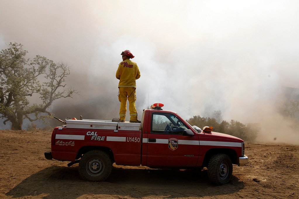. Cal Fire captain Gino DeGraffenreid uses a vantage point on his truck to monitor a firing operation west of Cachagua on Tuesday, August 2, 2016.  The Soberanes Fire was 45,800 acres and 25% contained  (Vern Fisher - Monterey Herald)