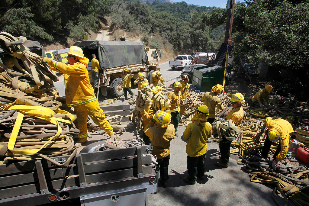 . Members of the California National Guard help load about five-miles of used wildland fire hose in Palo Colorado Canyon on Saturday, August 6, 2016.  The Soberanes Fire is currently at 55,600 acres and has a 40% containment.  (Vern Fisher - Monterey Herald)