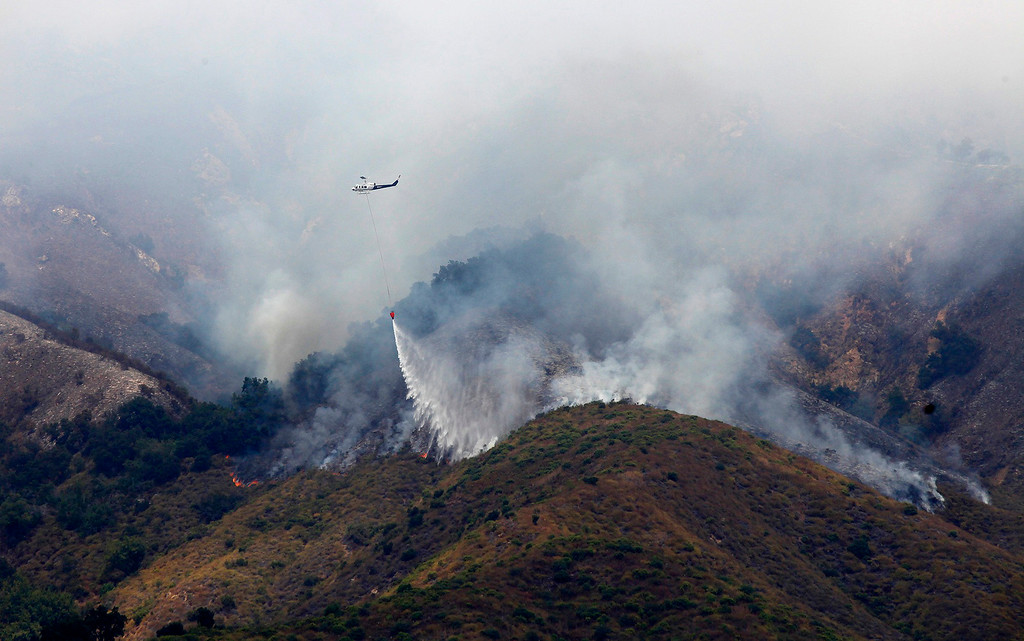 . A helicopter makes a water drop on the Soberanes Fire as it burns on the west slope of Mt. Manuel in the Pfeiffer Big Sur State Park on Tuesday, August 9, 2016.  The Soberanes fire has burned 67,000 acres and is 50% contained.  (Vern Fisher - Monterey Herald)