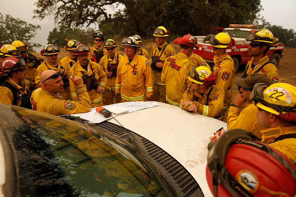 . Cal Fire captain Gus Boston (left) meets with his crew to discuss a firing operation west of Cachagua on Tuesday, August 2, 2016.  The Soberanes Fire was 45,800 acres and 25% contained  (Vern Fisher - Monterey Herald)
