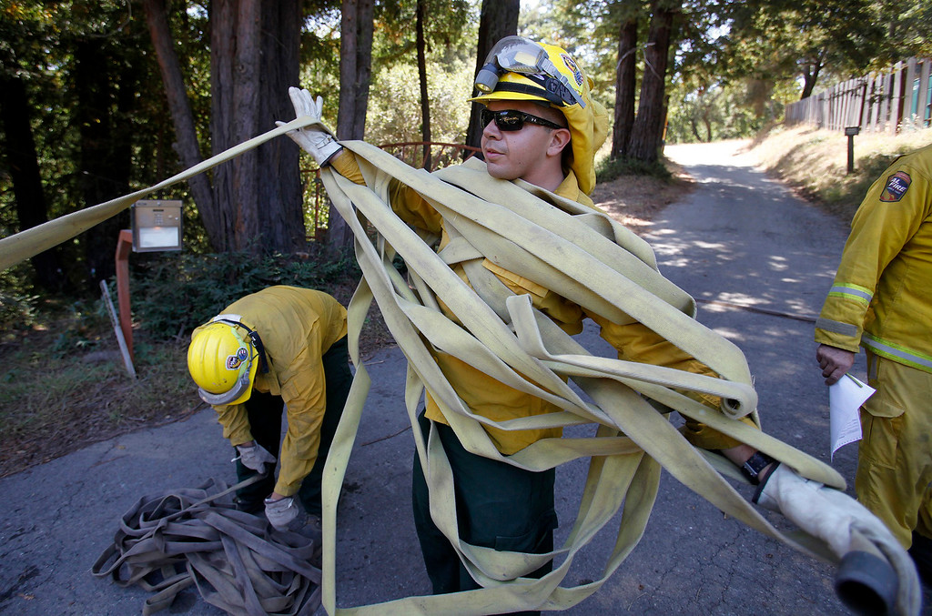 . Victor Lopez with the California National Guard helps load wildland fire hose in Palo Colorado Canyon on Saturday, August 6, 2016.  The Soberanes Fire is currently at 55,600 acres and has a 40% containment.  (Vern Fisher - Monterey Herald)