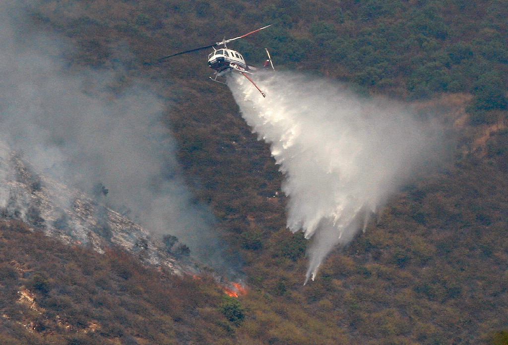 . A helicopter makes a water drop on the Soberanes Fire as it burns on the west slope of Mt. Manuel in the Pfeiffer Big Sur State Park just above the popular Mt. Manuel trail on Wednesday, August 10, 2016.  The fire has burned 68,698 acres and is 50% contained.  (Vern Fisher - Monterey Herald)