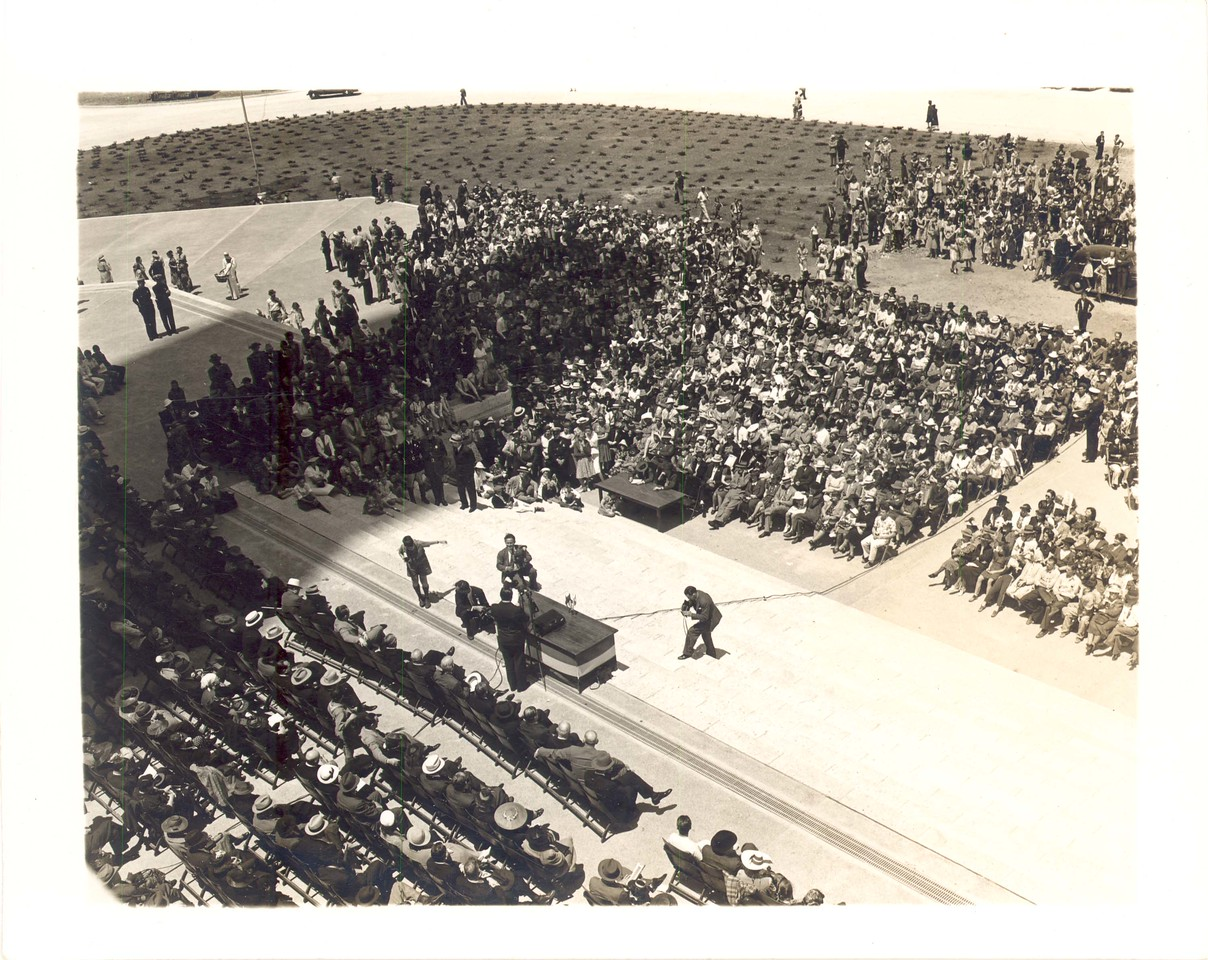 The crowd during Gov. W. Lee O'Daniel's speech at noon on April 21, 1939.  The bright sunshine caused many of the men to keep their hats on, a breach of etiquette for those seated on the platform.  Others in the audience shaded their eyes with their programs.