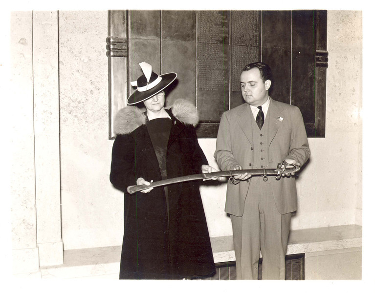 The foundation of the museum's collections came from gifts of artifacts and documents donated in early 1939 from a large number of people, including Hill.  Here, Jeanne Sully Smyth presents a Mexican army saber and scabbard to museum director Ike Moore for the museum.