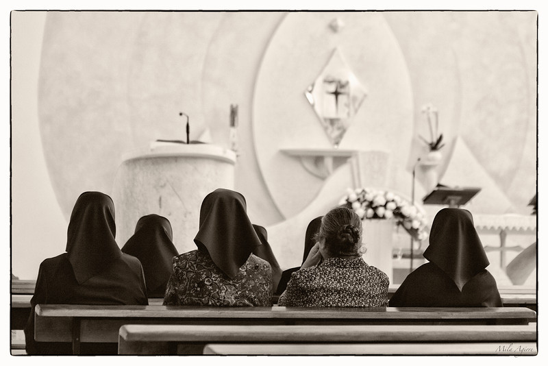 Praying the mass in Orgosolo (Sardinia). Famous because political paintings can be found on walls all over the village, it also maintains a strong identity and traditions like these ladies' clothings.