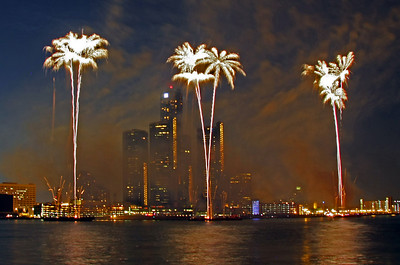 Fireworks are fired from three barges anchored in middle of river.