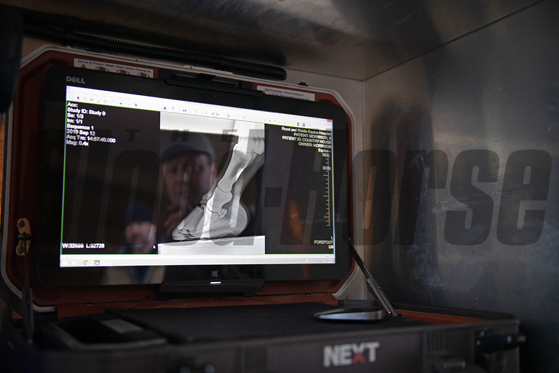 Initial treatment and xray review: Country House radiograph xray from September 12 2019, is reviewed by Scott Morrison DVM (right in reflection) and Guiness McFadden at Blackwood Stables on<br /> Feb. 28, 2020 Blackwood Stables in Versailles, KY.