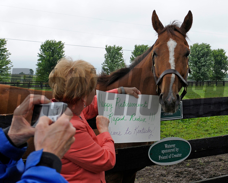 Caption:  fan with sign has her photo taken<br /> Rapid Redux after his recent arrival at Old Friends near Georgetown, Ky. on June 1, 2012.<br /> RapidRedux image383<br /> PHoto by Anne M. Eberhardt