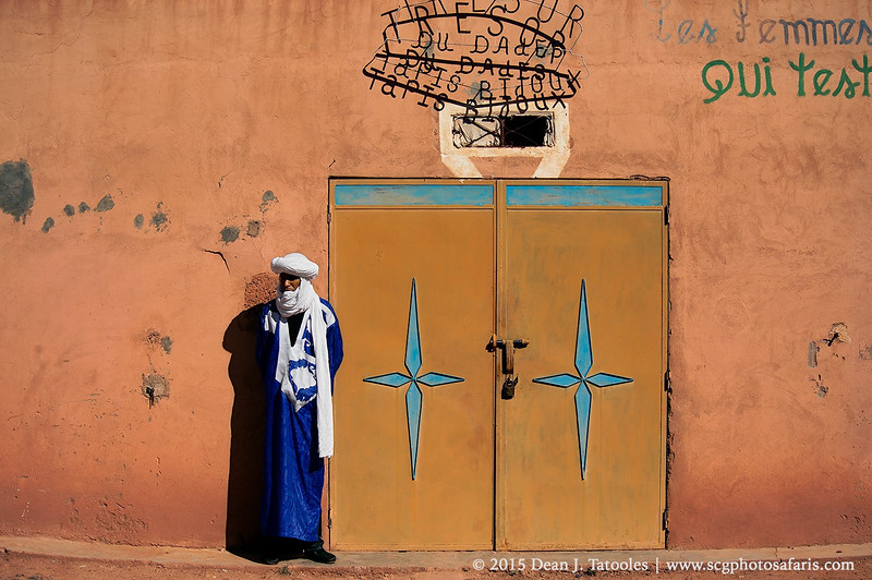 Photo Credits: Dean J. Tatooles; Southern Cross Galleries  | Our worthy guide, Ali, poses for a shot next to some colorful doors in a small village high up in the Atlas Mountains in Morocco.