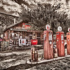 """Frontier Gas Station"" was photographed in Northern New Mexico. For this 8 exposure HDR photograph, I converted the original color image into a rich sepia, and allowed the red from the old gas pumps to shine through with the red from the Coca Cola sign and cooler, as well as other red objects. I love how the red turned out against that great sepia color."