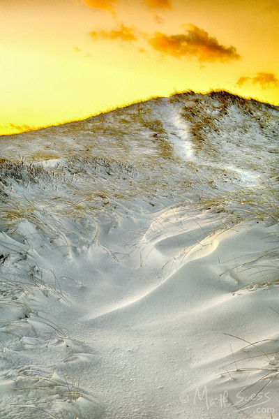 The sun sets over a sand dune covered in snow at Sandy Neck Beach in Barnstable on Cape Cod, Massachusetts.