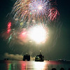 Fireworks explode above ferry boats during Forth of July celebrations above Hyannis Harbor on Cape Cod, Massachusetts as people look on along the shoreline.