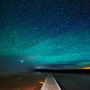 At Yellowstone National Park, Wyoming, Grand Prismatic Spring with boardwalk at the Midway Geyser Basin with stars and the Milky Way.