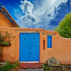 An adobe house with blue doors in Taos, New Mexico