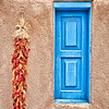 """""""Ristras and Window"""" was photographed in Taos, New Mexico, and not too far away from Santa Fe. The red peppers hung on the adobe wall gives a great contrast to the blue window."""