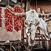 """""""Ristras and Skulls"""" was photographed in downtown Santa Fe near the Plaza. I love how the color of the red peppers comes through in this photo that has a primarily sepia tone to it."""