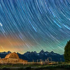 The John Moulton Barn on Mormon Row in Grand Teton National Park during a long exposure of the night sky.