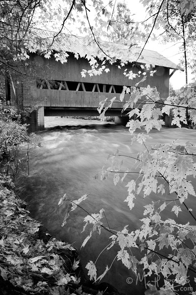 Fall foliage and a wood covered bridge along a river in Central Vermont.