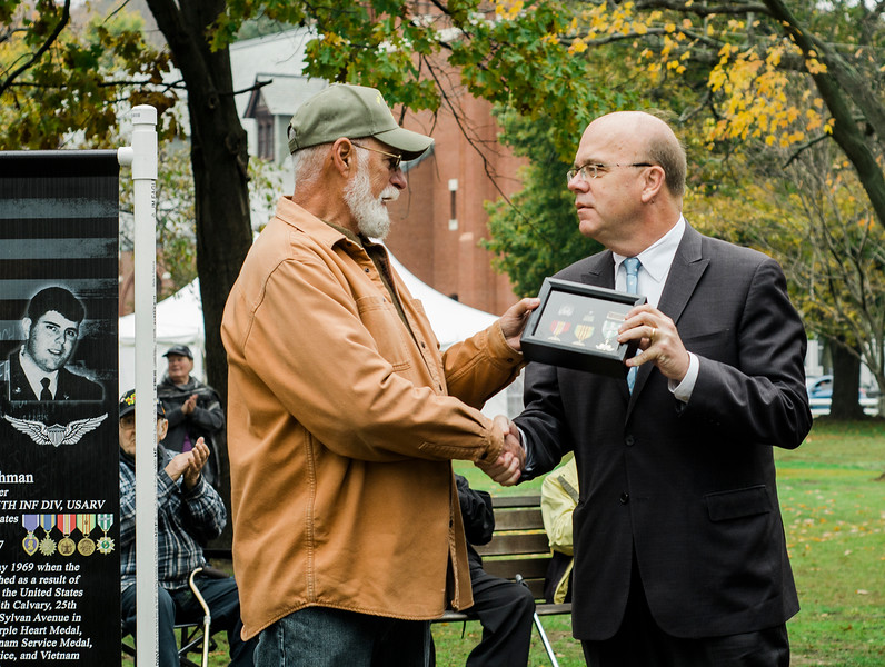 "Congressman James McGovern presents overdue Vietnam War medals to John Coleman, US Army retired, during the ceremonies at ""The Wall That Heals"" at Carter Park on Thursday morning. The wall, a 250-foot replica of the Vietnam Wall, is on display at Carter Park and ceremonies will be held daily through Saturday evening. SENTINEL & ENTERPRISE / Ashley Green"