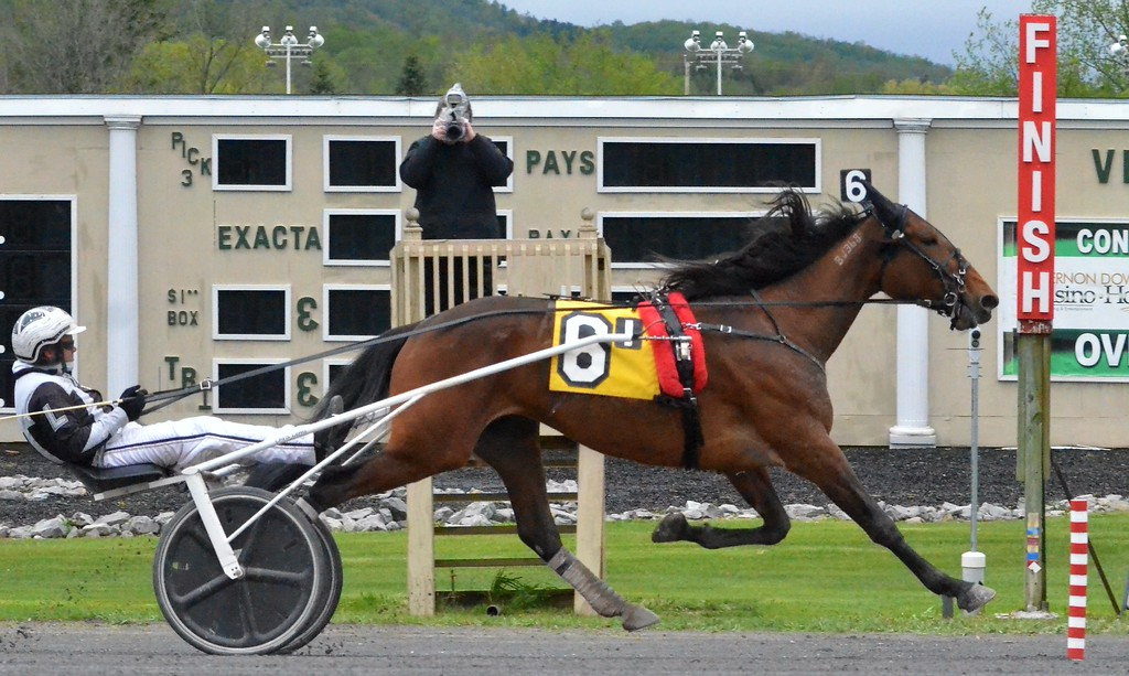 . KYLE MENNIG - ONEIDA DAILY DISPATCH Chris Lems drives Gimme The Cash past the finish line to win the first race of the season at Vernon Downs on Friday, May 5, 2017.