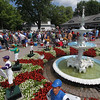 Spencer Tulis <br /> Racing fans wait at the Clubhouse entrance Friday as the first day of Saratoga's Thoroughbred Summer Meet got underway. In the foreground are the fountain with lawn jockeys adorned with all the Grade I winner's silks colors from last year's meet.