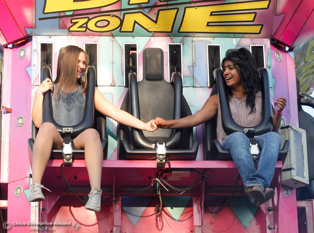 ". Kate Pilgram and Natalia Castillo hold hands as they brave the ""Drop Zone,\"" on the opening night of the 2017 Butte County Fair Thursday August 24, 2017 in Gridley, California. (Emily Bertolino -- Mercury-Register)"