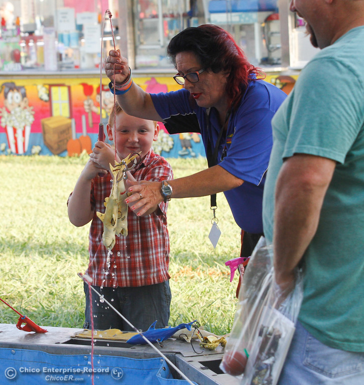 . Shellie Miramontes helps Chase Cari, 6, pull out his big catch at a game booth on the opening night of the 2017 Butte County Fair Thursday August 24, 2017 in Gridley, California. (Emily Bertolino -- Mercury-Register)