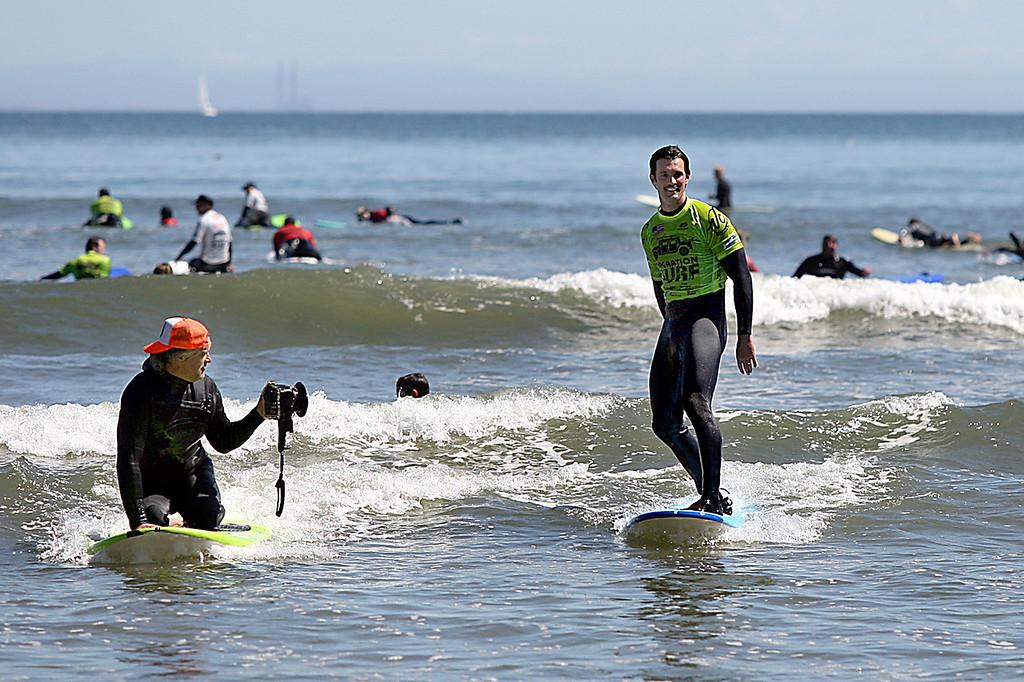 . Mark Dahl from Oakland gets his picture taken by Operation Surf Santa Cruz photographer Ira Amerson Monday afternoon at Cowell surf break. (Dan Coyro -- Santa Cruz Sentinel)