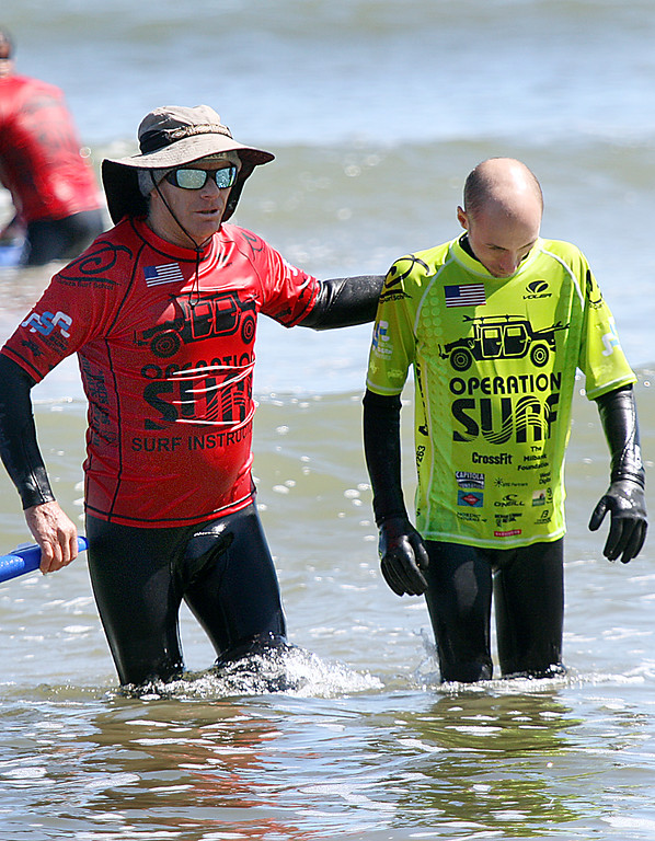 . Santa Cruz surf pro Richard Schmidt accompanies Damon Sadowski onto Cowell beach after a successful surf session Monday as part of Operation Surf Santa Cruz. (Dan Coyro -- Santa Cruz Sentinel)