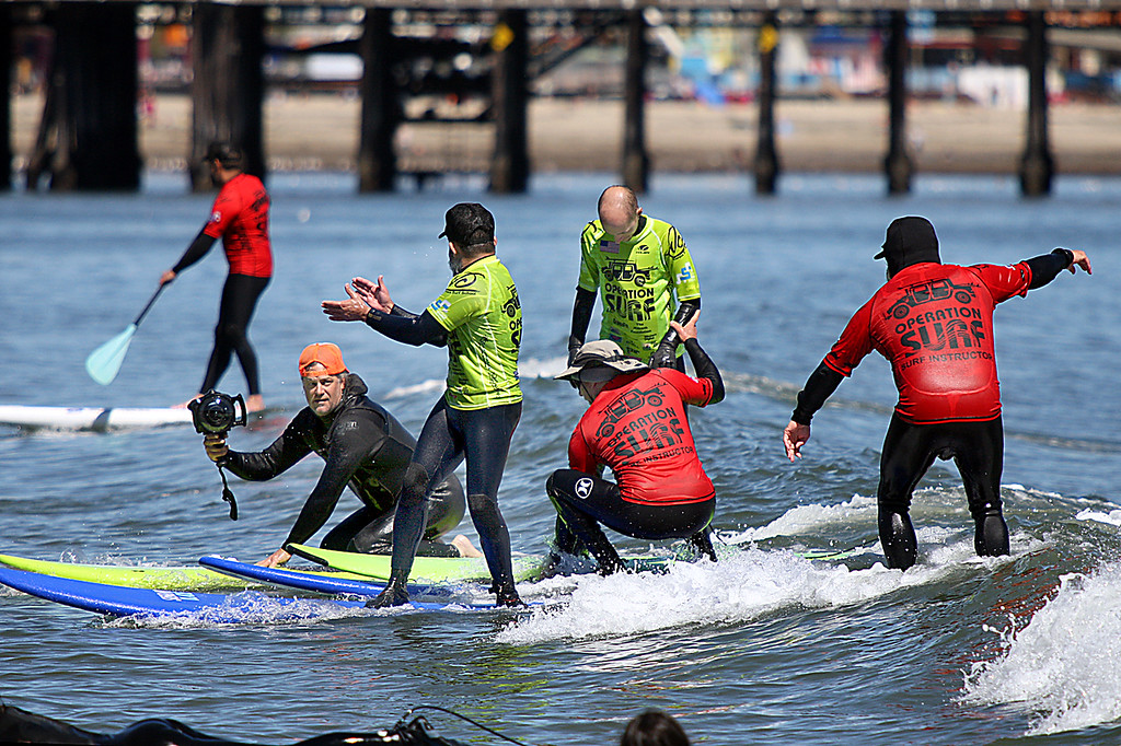 . Operation Surf Santa Cruz photographer Ira Amerson shoots pictures of Sam Rosales surfing for the first time in his life as Richard Schmidt gives a hand to Damon Sadowski Monday at Cowell surf break. (Dan Coyro -- Santa Cruz Sentinel)