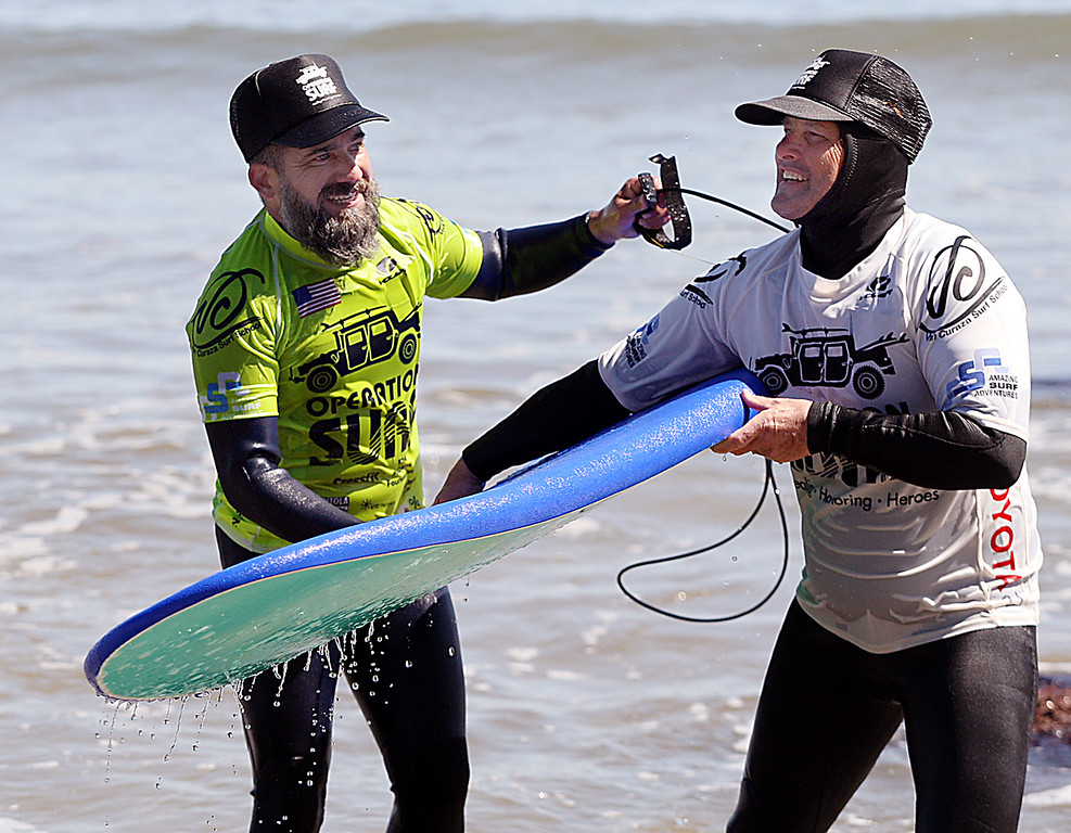 . After catching and riding many waves on his first day of surfing Monday, military vet Sam Rosales, left, hands his board to Rob Jarvis of Operation Surf Santa Cruz. (Dan Coyro -- Santa Cruz Sentinel)