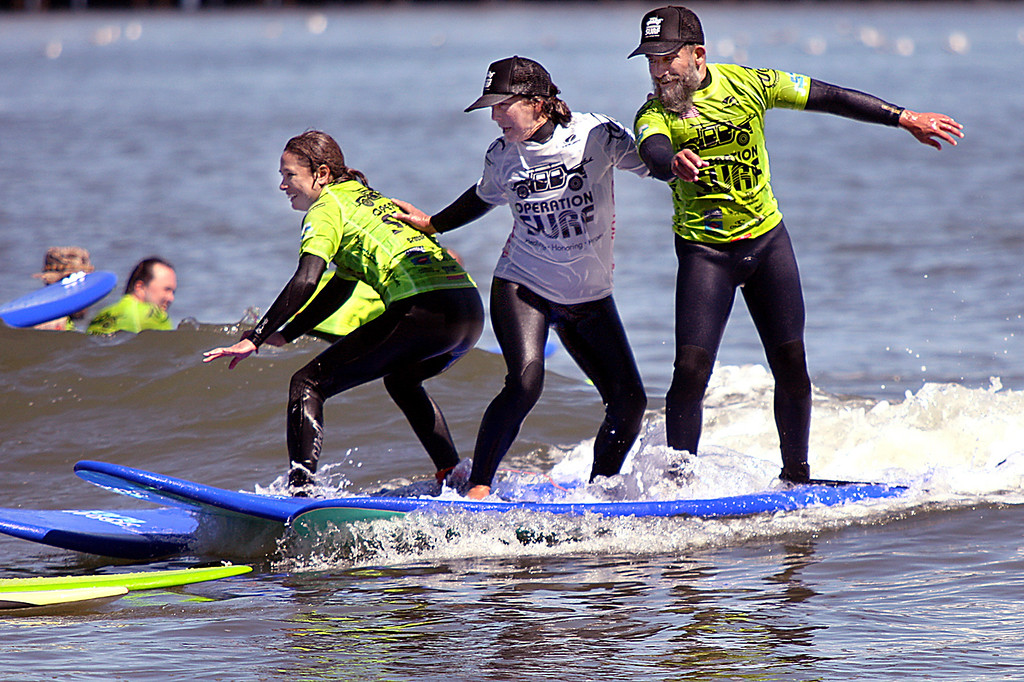. Operation Surf Santa Cruz coach Sophia S. has her hands full with veteran Sam Rosales, at right, and a first-time surfer, at left as all three ride a wave at Cowell surf break Monday afternoon. (Dan Coyro -- Santa Cruz Sentinel)