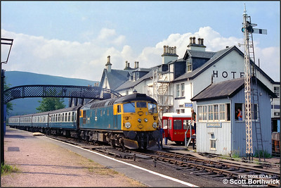 26035 working 2K08 1045 Inverness-Kyle of Lochalsh on 25/07/1983 had developed a hot axle box by the time it reached Achnasheen, where it was booked to cross 2N20 1110 Kyle of Lochalsh-Inverness hauled by 37025. 26035 was detached from its train and run into the adjacent platform allowing 37025 to be detached from 2N20 and run onto 2K08. 26035 then ran back onto 2N20 and hauled it into Achnasheen station. 37025 then set off back to Kyle of Lochalsh whilst 26035 was removed from its new train and dumped in a siding. Assistance for 2N20 arrived some two hours later in the form of 37183 from Inverness TMD. Here, 26035 is seen being detached from the Inverness bound service shortly after 37025 had departed to Kyle. Note the Royal Mail Post Bus awaiting the solitary mailbag from Inverness left on the westbound platform.