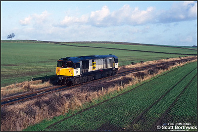58036 traverses the ex Midland Railway Clowne Branch approaching Oxcroft Colliery Branch Junction whilst running light loco from Shirebrook TMD to Barrow Hill TMD on 19/11/1992. By this time light locomotives were pretty much the only through traffic on this section of line from Cresswell Jnct to Seymour Jnct. In the mid 1990's a serious underground fire that proved difficult to control threatened to undermine the line. This, coupled with the expensive requirement to replace the points connecting the branch at Creswell Jnct would lead to the closure of the line. The points at Cresswell Jnct were relaced with plain line, as were those at Oxcroft Colliery Junction. With track now lifted the trackbed has become the Clowne Branch Greenway, a traffic free cycling and walking route.