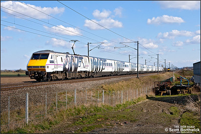 91107, renumbered as 91007 and named 'Skyfall', in connection with its advertising livery promoting the release of the James Bond movie Skyfall on DVD & BluRay, passes Broad Fen Lane, Claypole whilst propelling 1A37 1515 Leeds-London King's Cross on 03/04/2013.