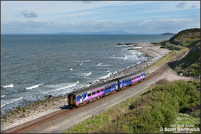 With the Scottish coastline of Dumfries & Galloway clearly visible across the Solway Firth, 156443 forms 2C39 0906 SO Whitehaven-Carlisle skirting the coast at Lowca on 30/05/2015.