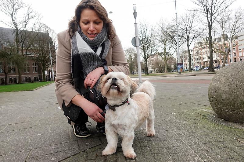 Nederland, Amsterdam, bij het tropenmuseum kom ik Mirte tegen met haar half blinde hondje Bruce, alias Broes. Broes liep 22 oktober  op de Dappermarkt met een enorme kap om zijn nek, hij was toen net geopereerd en zijn linkeroog kwijtgeraakt, maar het zou allemaal goedkomen en zie daar.10 maart 2017, foto: Katrien Mulder