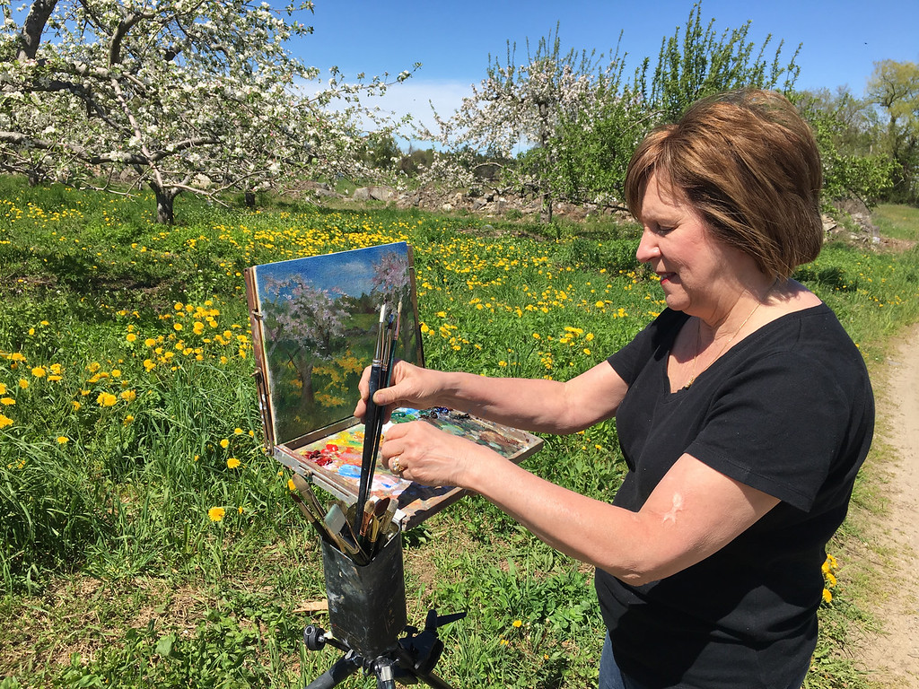 . Mary Rose O\'Connell put her brushes away after completing the day\'s work on her canvas. Photo by Mary Leach