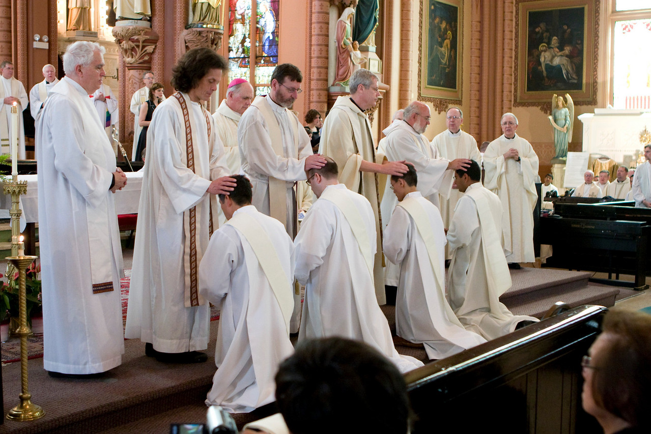Among those concelebrating, Jesuits Joseph Daust, Benjamin Jimenez, Mitch Pacwa, Walter Deye, and John Ferone lay their hands on Glen, Bill, Peter, and Charlie.