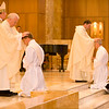 In the tradition of the apostles, the ordaining Bishop and fellow priests lay hands on the heads of the candidates and pray silently as a sign of the conferral of the Holy Spirit, who ordains one to serve in Holy Orders.