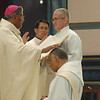 In the tradition of the apostles, the ordaining bishop and fellow priests lay hands on the head of the candidate and pray silently as a sign of the conferral of the Holy Spirit, who ordains one to serve in Holy Orders. Here The Most Rev. William D'Souza, archbishop of Patna, confers a blessing on Fr. Joel Medina, SJ, of Jackson, Michigan, at the Ordination Mass at St. Xavier Church, Cincinnati, Ohio, on Saturday, June 11, 2011.