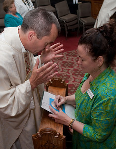 Father Thomas Zuhuta blesses Shawne Giustra at the reception.  (Photo by Thomas Spink)