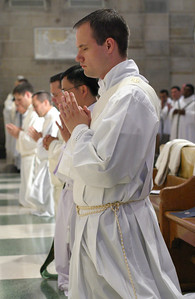 Llane Briese kneels with his fellow ordination candidates as Archbishop Gregory conducts the prayer of consecration.