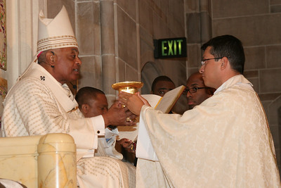 As a sign of the new priest's office, Archbishop Gregory presents the chalice and paten to Father Mario Lopez.