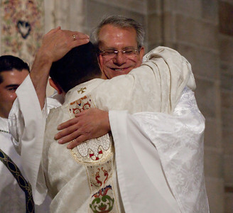 Father Carlos Vargas Silva (back to camers) is embraced by fellow priests. (Photo by Thomas Spink)