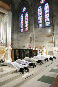 (L-r) Rev. Mr. Llane Briese, Thang Pham, Carlos Vargas, Thomas Zahuta, Michael Silloway and Mario Lopez prostrate themselves on the altar during a moment of prayer for the candidates.